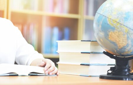 Education concept back to school and business study global world / Young woman student campus reading a book in library with book stacked and earth globe model map