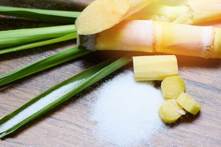 sugar cane and white sugar on wooden table background