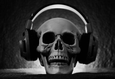 Schädelmusik mit Kopfhörer / Menschlicher Schädel, der auf Halloween-Party und Licht auf dunklem Hintergrund Musik-Kopfhörer hört