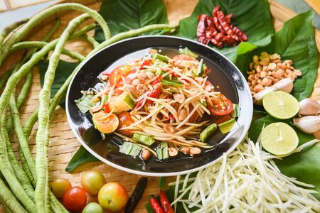 Papaya salad served on wooden dining table  Green papaya salad spicy thai food on plate with yardlong bean herbs and spices ingredients chilli tomato peanut garlic - Som tum Thai menu Asian food Stockfoto