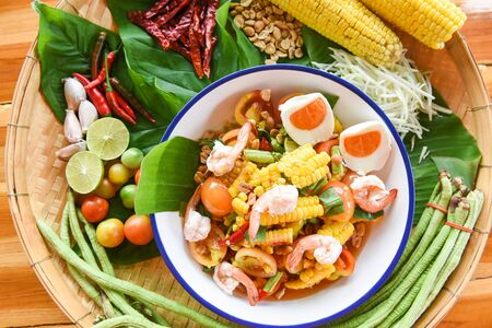 salad corn salted egg shrimp spicy with fresh vegetables herbs and spices ingredients with chilli tomato peanut garlic served on plate / Corn Salad Papaya Som tum Thai menu Asian Standard-Bild - 128736443