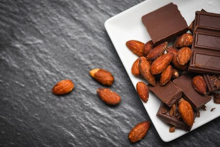 chocolate bar with almonds nut on white plate on the dark background  chunks candy sweet dessert and snack Stockfoto