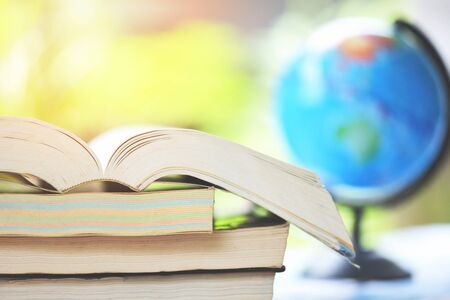 Education concept back to school and business study global world  open book in the table with book stacked and earth globe model map nature background