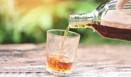 Pouring whiskey or alcohol drink from bottle to glasses on wooden  background / Pour liquor Standard-Bild - 128736932