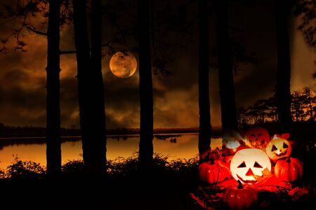 Halloween pumpkin lantern on outdoors with tree and full moon on river / head jack o lantern evil faces spooky holiday decorate on halloween background moonlight Standard-Bild - 128736955