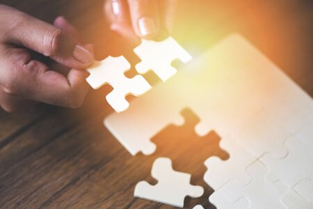 jigsaw puzzle with woman hand connecting jigsaw piece with sunlight  Business solutions partnership success and strategy concept