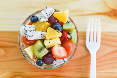 Fruit salad bowl fresh summer fruits and vegetables healthy organic food strawberries orange kiwi blueberries dragon fruit tropical grape pineapple tomato lemon with fork on dining table