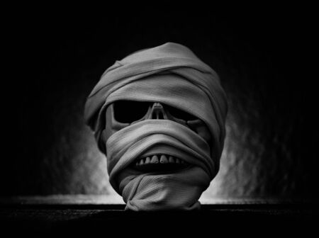 Mummy covered by clothes in skull decorated at halloween cosplay and light on dark background Standard-Bild - 128737027