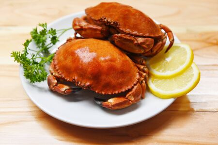 Cooked crab on plate with lemon herbs and spices on the wooden dining table background  Seafood boiled red stone crabs salad Stockfoto