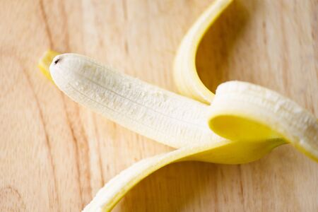 Banana peel / Close up of fresh ripe a banana fruit peeled on wooden board Standard-Bild - 128737037
