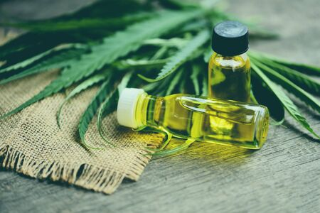 Cannabis oil on bottle products wooden background - CBD oil extract from cannabis leaf Marijuana leaves for Hemp medical healthcare natural selective focus Standard-Bild - 128737045