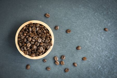 Roasted coffee beans on wooden bowl and dark background Standard-Bild - 128737046