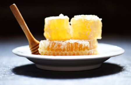 Fresh honey healthy food yellow sweet honeycomb slice with wooden dipper on white plate and dark background