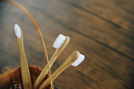bamboo toothbrush in basket eco natural plastic free items on rustic background  Zero waste bathroom use less plastic concept
