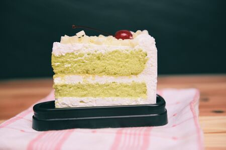 Green cake slice with cherry fruit and cream on white palte on the table  Delicious green tea cheese cake
