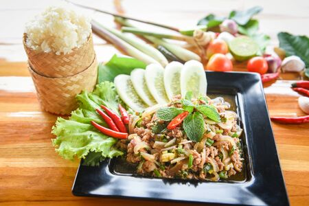 Spicy minced pork salad Thai food served on table with herbs and spices ingredients sticky rice Tradition northeast food Isaan delicious on plate with fresh vegetables Larb Pork Thai menu Asian food
