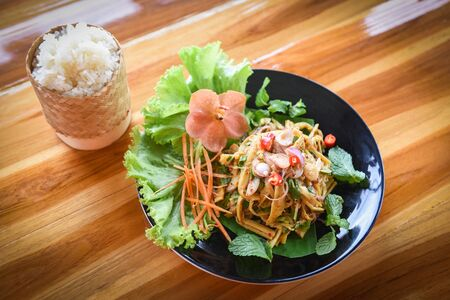 Thai bamboo shoot spicy salad served on plate on the wooden table and ticky rice / Bamboo shoot dry soup shredded cooked with herbs and spices ingredients and fresh lettuce vegetable Standard-Bild - 128737180