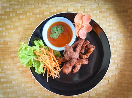Deep fried beef or pork with sauce and fresh vegetable on plate in the wooden table top view / Thai Fried Sun Dried Beef Asian food Standard-Bild - 128737176