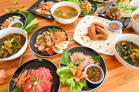 Table food served on plate  Tradition northeast food Isaan delicious on plate with fresh vegetables - Many variety various Thai menu Asian food on a wooden table , top view