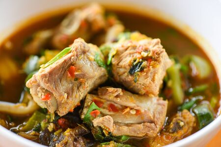 Pork rib curry spicy soup  pork bone with hot and sour soup bowl with vegetables Tom Yum thai herbs , Thai Food Asian