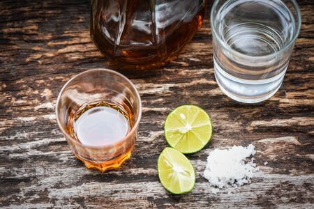 alcoholic drinks and lemon salt on rustic wood background / brandy in a glass with alcohol bottles and water - vodka rum cognac tequila and whiskey concept Standard-Bild - 128737190