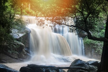 Waterfall landscape beautiful with sunlight rays in the river stream on the mountain with tree and the rock stone foreground  waterfall thailand tropical forest