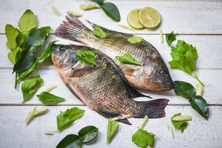 Tilapia fish freshwater and lemon lime herb vegetable for cooking food in the asian restaurant  Fresh raw tilapia on wooden background