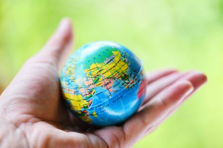 The world in the hand with nature background / hand holding globe with map and environment green planet save the earth concept