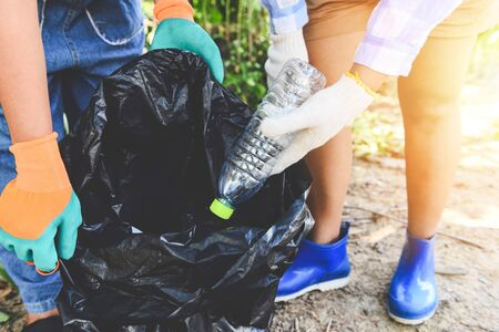 Group of young women volunteers helping to keep nature clean and picking up the garbage plastic bottle from park / Recycling and waste reduction techniques that help the environment