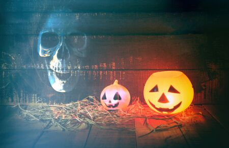 Halloween pumpkin lantern with dry straw on wooden and ghost scary skeleton grim reaper with skull / head jack o lantern evil faces spooky holiday decorate on halloween background