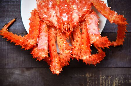 Fresh Alaskan King Crab Cooked steam or Boiled seafood on plate and wood background , top view - Red crab hokkaido
