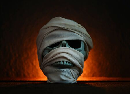 Mummy covered by clothes in skull decorated at halloween cosplay and light on dark background Standard-Bild - 129243346
