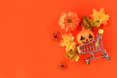 Halloween shopping holiday concept  accessories with spider pumpkin jack o lantern and leaves autumn in a shopping cart on orange background , top view aerial image flat lay copy space