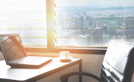 coffee cup on the table in a office with laptop on table in office  Wooden table in sunny office with windows sunlight