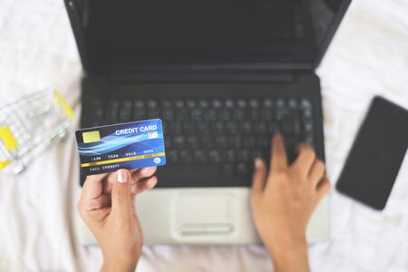 Woman hands holding credit card and using laptop for online shopping with shopping cart on the bed  people paying technology money wallet online payment at home , Credit card mockup Stockfoto