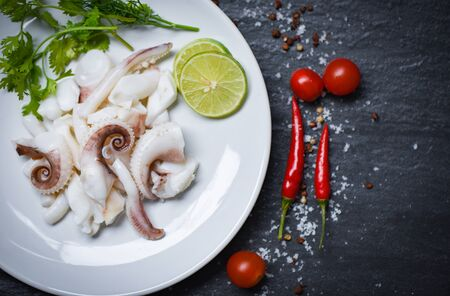 squid salad with lemon herbs and spices on dark background top view / Tentacles octopus cooked appetizer food hot and spicy chilli sauce seafood cooked served on plate in the restaurant