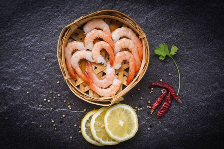 fresh shrimps on bamboo steamers with spices lemon chilli on the dark plate  boiled peeled shrimp prawns cooked in the seafood restaurant Imagens