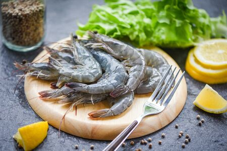 raw shrimps on wooden cutting board plate  fresh shrimp prawns for cooking with spices lemon on dark background in the seafood restaurant Imagens