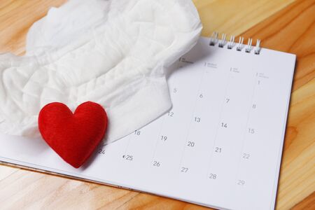 Sanitary napkin or feminine sanitary pad on calendar with red heart  Female hygiene means women Period Product absorbent sheets