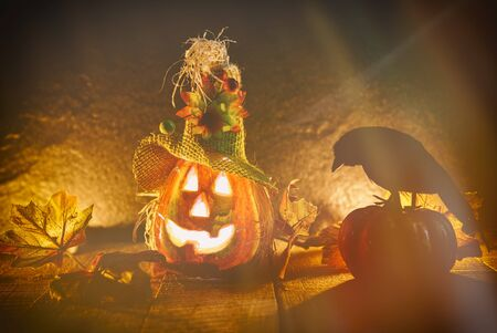 Halloween pumpkin scarecrow lantern with dry straw on wooden / head jack o lantern evil faces spooky holiday decorate on halloween background and crow sitting on pumpkin