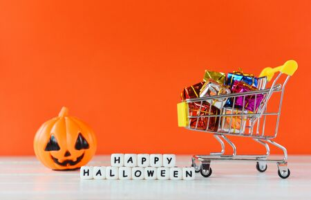 Halloween shopping holiday concept  word blocks happy halloween decorations and pumpkin jack o lantern with gift box in a shopping cart on orange background