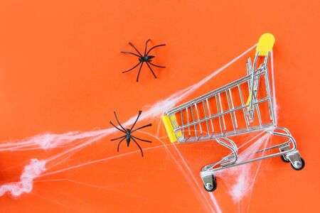 Halloween shopping holiday concept  accessories with black spider and spider web on shopping cart on orange background , top view aerial image flat lay