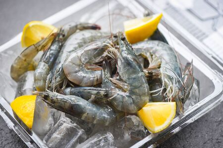raw shrimps on ice with spices lemon on the dark plate  fresh shrimp prawns in box at restaurant or seafood market