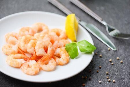 shrimps served on plate with Lemon, Herb, Pepper on white plate  boiled peeled shrimp prawns cooked in the restaurant Imagens