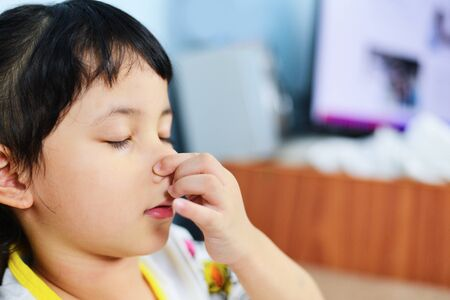 Asian little girl sick with hand holding the nose get cold and blow nose the flu season  child runny nose and sneezing blowing their nose and fevers at home Stock fotó