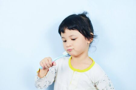 Asian little girl brushing teeth with toothbrush in hand dental hygiene  child dont brush teeth , selective focus 写真素材