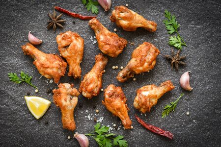 Fried chicken wings with lemon garlic chilli herbs and spices on black plate top view  Baked chicken wings BBQ 스톡 콘텐츠