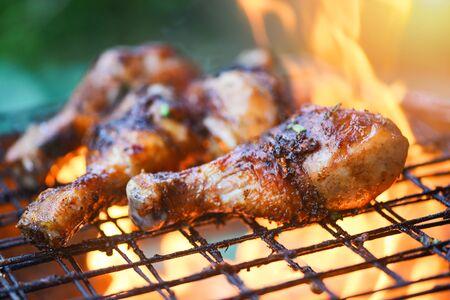 Cosce di pollo alla griglia barbecue con erbe e spezie / Gustose cosce di pollo alla griglia con fiamme di fuoco marinate con ingredienti che cucinano picnic all'aperto Archivio Fotografico