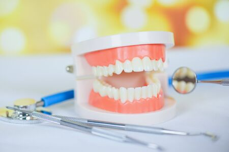 dentist tools with dentures dentistry instruments and dental hygienist checkup concept with teeth model and mouth mirror oral health and stethoscope doctor Stock Photo - 129779474