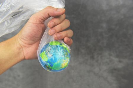 Plastic world or World Environment Day Concept  Hand holds the planet earth in a plastic bag ban say no plastic pollution zero waste recycle